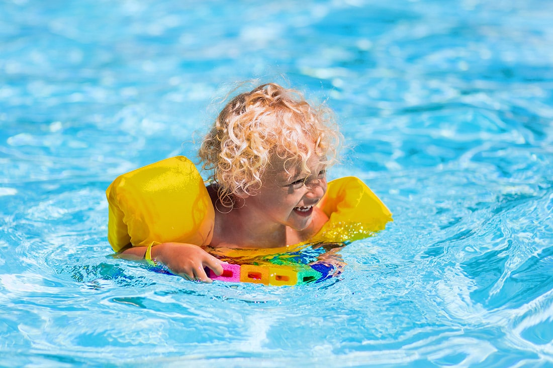 Small kid wearing floaties in the pool